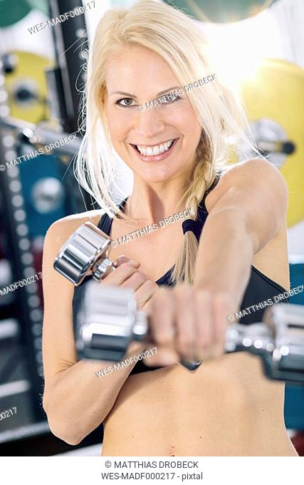 Portrait of young woman training with dumbbells at gym