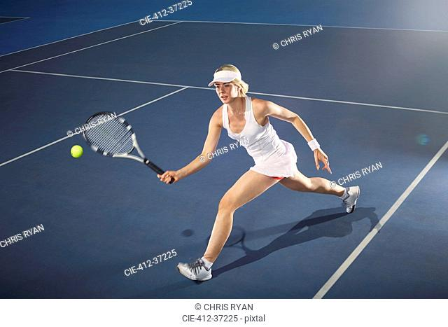 Young woman playing tennis on tennis court