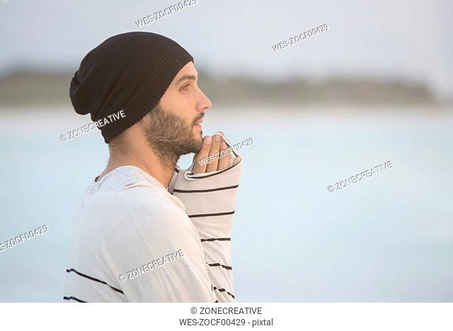 Young man standing on the beach, looking pensive