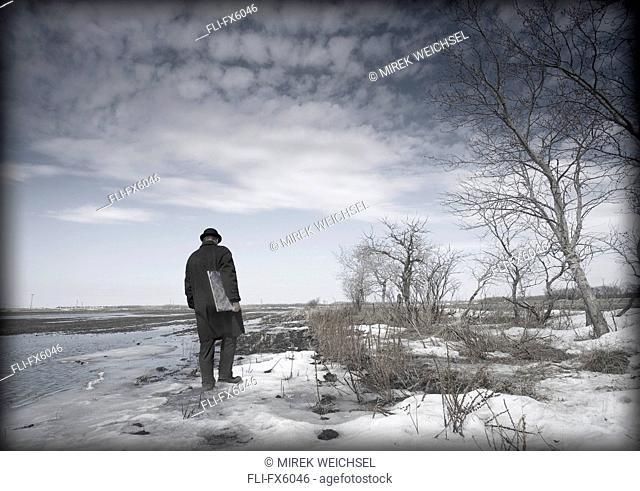 Man in Hat and Coat Walking in Field in Winter, Winnipeg, Manitoba