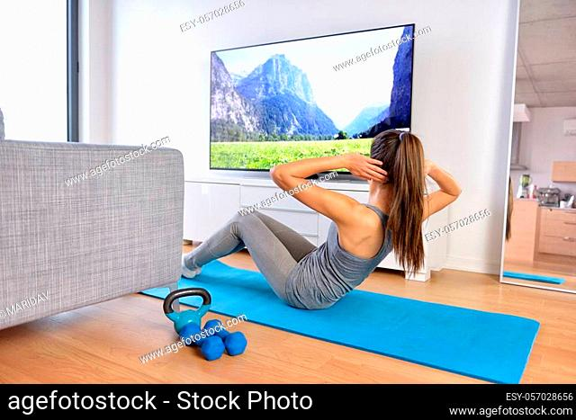 Home workout - woman exercising in front of a flat screen watching a fitness program or exercising during a TV show lying on a yoga mat in front of the sofa in...