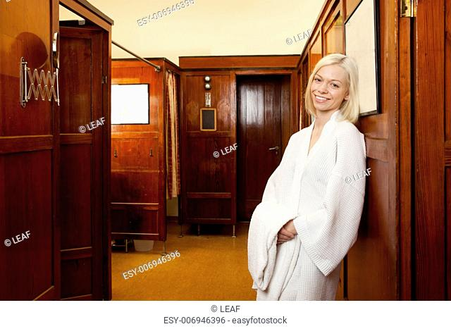 Portrait of an attractive blonde woman in an old 1920s style european spa and bath house
