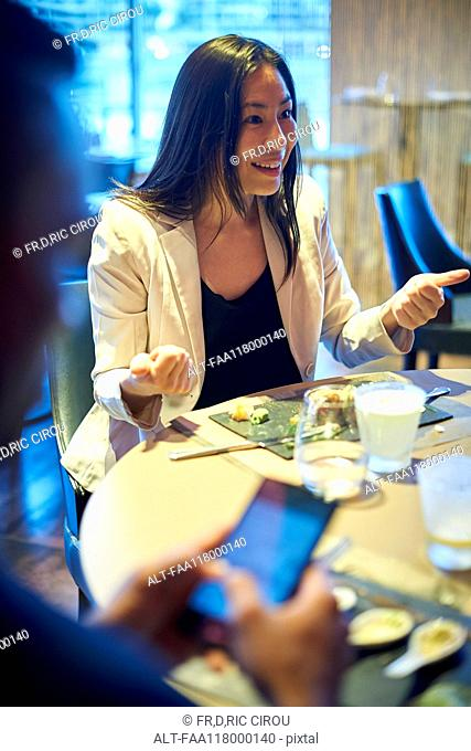 Smiling business woman sitting in bar