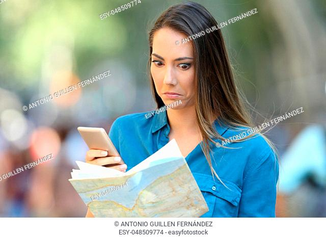 Confused tourist trying to find location on a map and a smart phone on the street