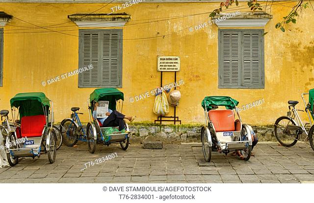 Cyclo drivers and yellow walls in the picturesque old town of Hoi An, Vietnam
