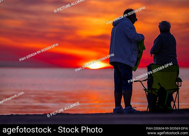 02 June 2020, Mecklenburg-Western Pomerania, Timmendorf (poel): Holidaymakers watch the sunset over the Baltic Sea from the beach on the island of Poel