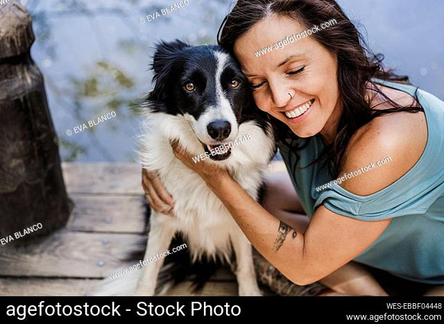 Smiling woman with eyes closed hugging pet dog while sitting on pier