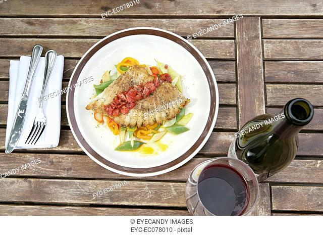 Fish dish with red wine at outdoor cafe