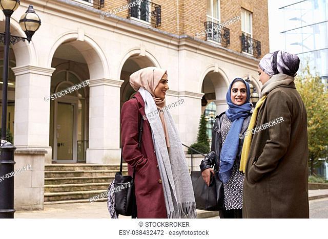 British Muslim Female Friends Meeting In Urban Environment