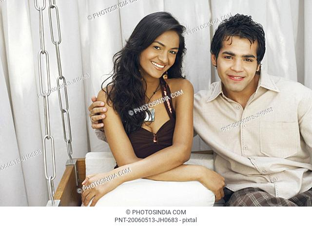 Portrait of a young couple sitting on a swing and smiling