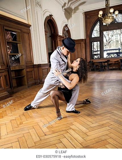 Full length of man and woman looking at each other while performing tango in restaurant