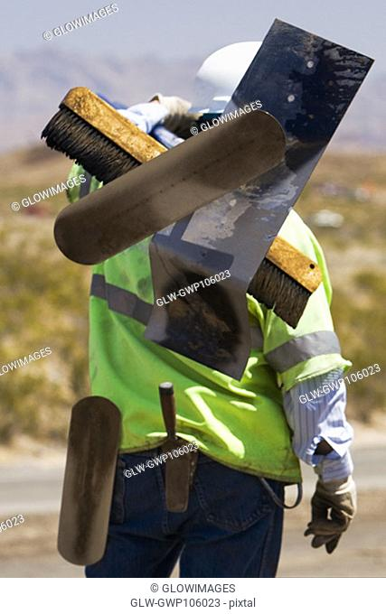 Rear view of a construction worker carrying hand tools on his shoulder