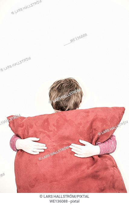 Sad little girl hiding behind a big red pillow. She is standing in front of a white wall with a lot of empty space that can be used as copyspace