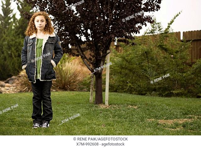 A growing young mixed race mexican & caucasian girl standing in front of a young sapling