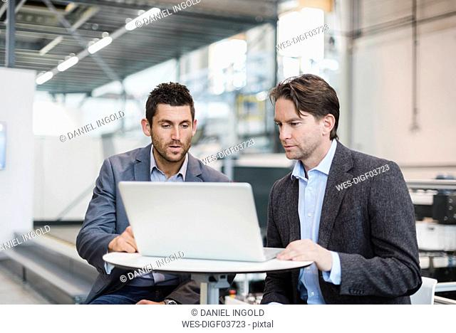 Two businessmen sharing laptop in factory