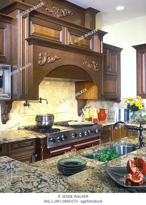 KITCHENS: Detail of cooking area with stove top and work island. Traditional, dark wood ornate exhaust hood, cream and brown veined marble