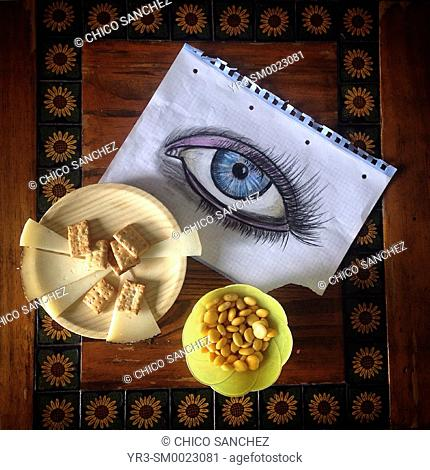 A painted eye and plates of lupins and cheese in Prado del Rey, Sierra de Cadiz, Andalusia, Spain