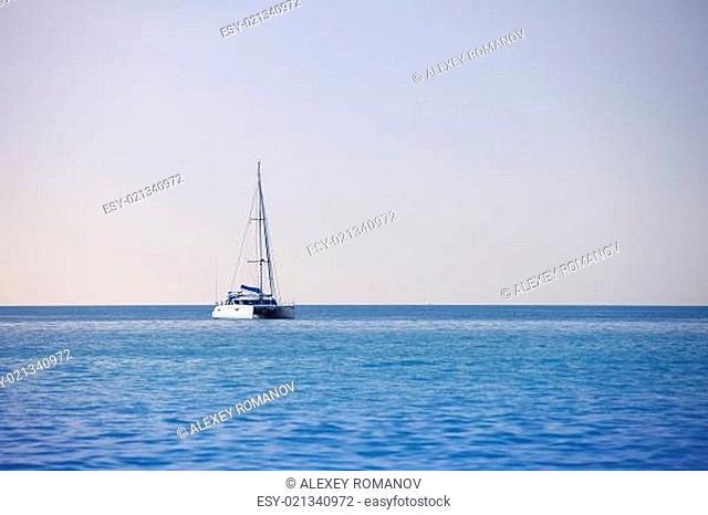 White sailing catamaran on calm sea
