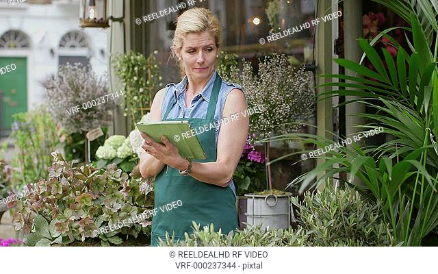 A Florist stands in the doorway of her shop typing into her digital tablet