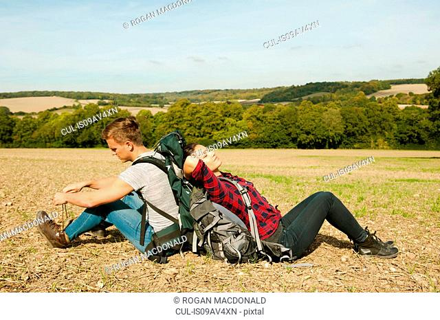 Young hiking couple sitting back to back in field, Great Missenden, Buckinghamshire, U.K
