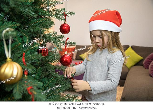 four years blonde child with red Santa Claus hat, decorating Christmas tree at home