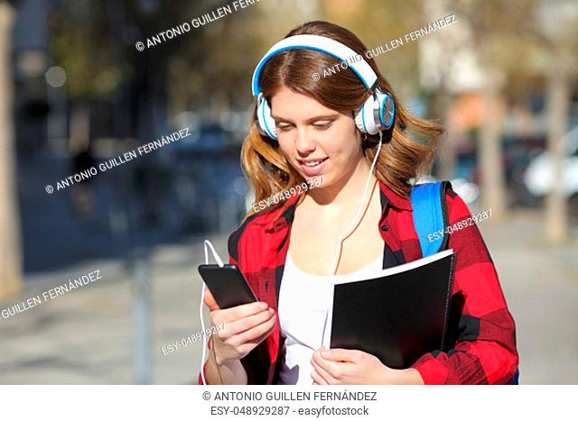 Student listens to music with headphones and smart phone walking in the street