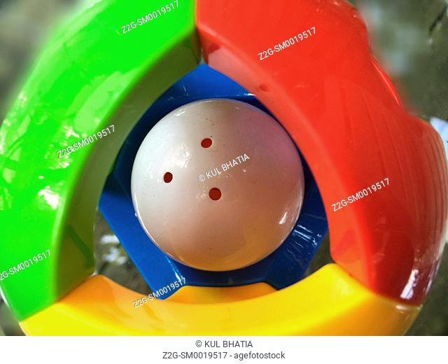 A Colorful plastic ball with triangular panels and a white rattling ball, Ontario, Canada