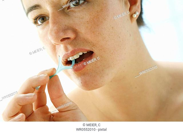 portrait of a young woman cleaning her teeth with dental floss