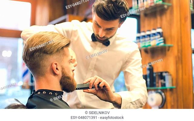 Young man sitting in a barbershop while barber working