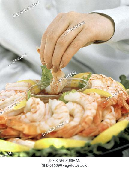 Hand Dipping a Shrimp into Cocktail Sauce