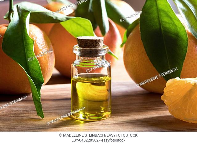 A bottle of tangerine essential oil on a wooden table, with fresh tangerines in the background