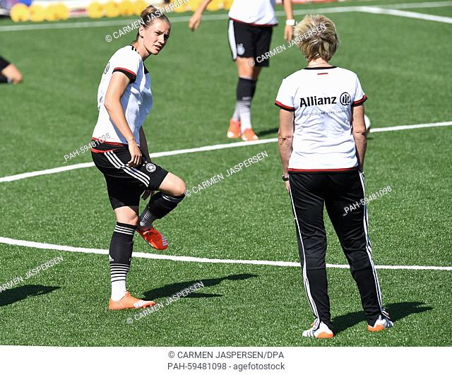 Germany's head coach Silvia Neid speaks to Simone Laudehr (L) during a training session at the FIFA Women's World Cup 2015 at the Avenue Bois-de-Boulogne