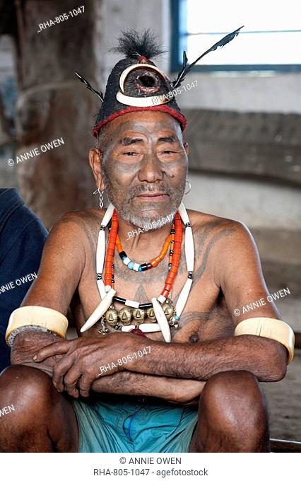 Naga head hunter, Wokshing Pensha, wearing Naga tribal necklaces and hat, and chest tattoo marking him as having taken a head, Nagaland, India, Asia