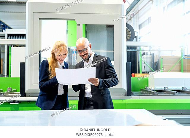 Smiling businessman and businesswoman looking at plan in factory