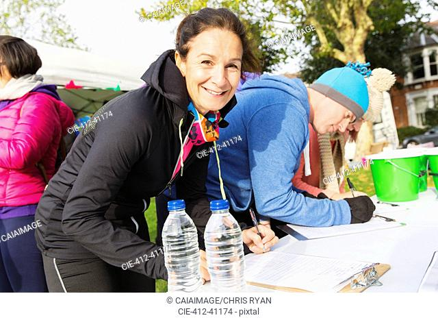 Portrait smiling female runner checking in at charity run in park