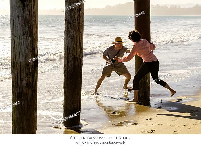 Middle aged man and woman frolicking and chasing each other around boardwalk piers at the beach