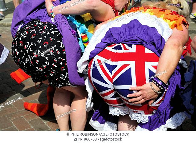 Rochester, Kent, England, UK. Sweeps Festival, 2013. Two women dances bending over to reveal colourful bloomers