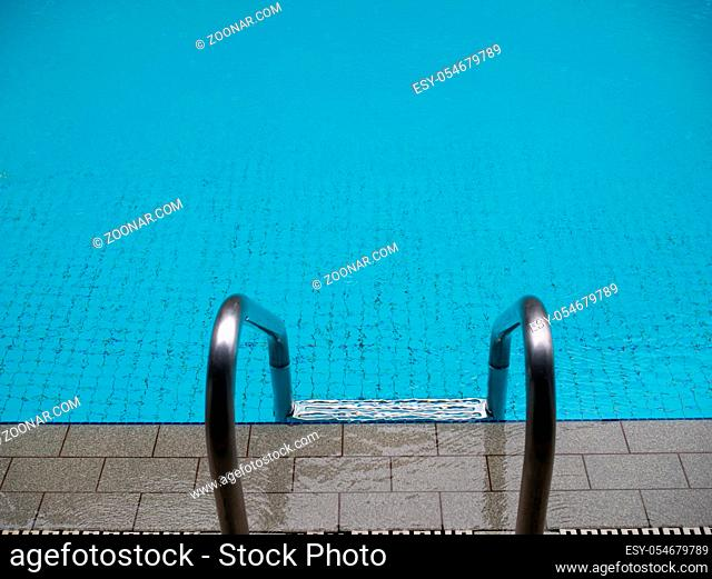 Photo of pool for swimming with blue water with ladder