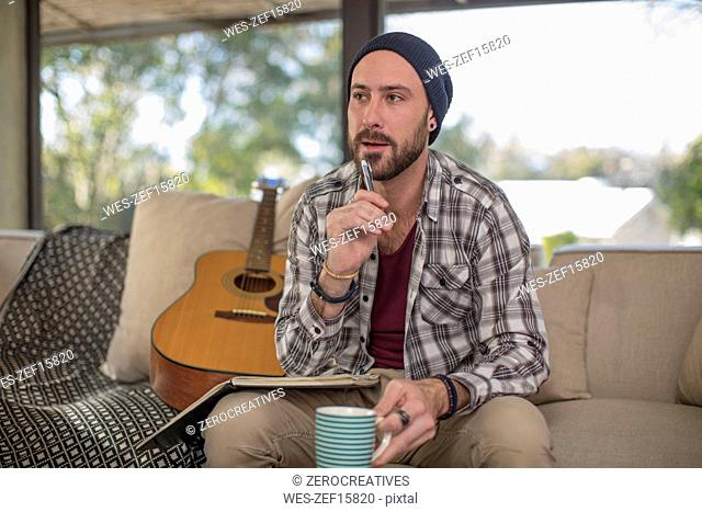 Young man at home sitting on couch with guitar taking notes