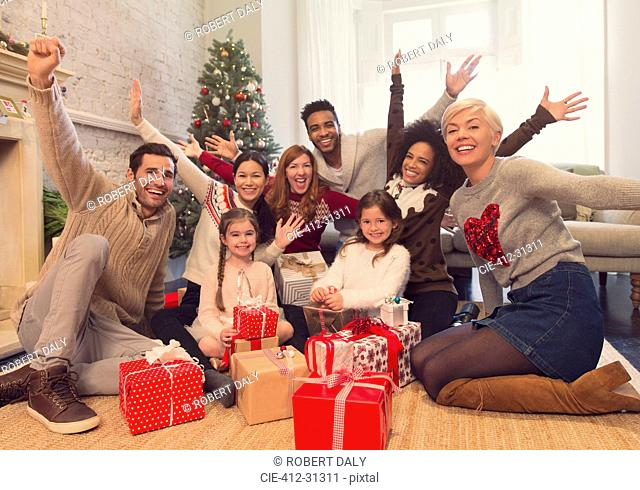 Portrait enthusiastic family and friends with Christmas gifts in living room