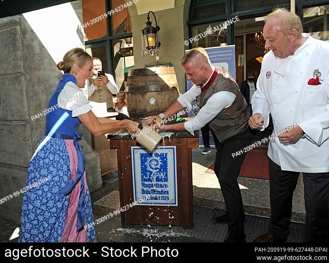 19 September 2020, Bavaria, Munich: Cabaret artist Monika Gruber tries to tap a barrel with the help of a waiter and star chef Alfons Schuhbeck (r) at the...