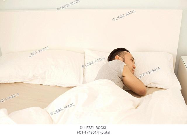 High angle view of young man sleeping in bed at home
