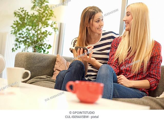 Two female friends, sitting on sofa, looking at smartphone