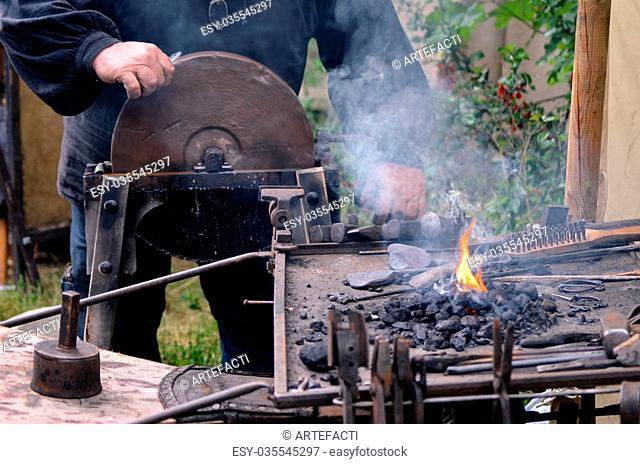Blacksmith working on metal medieval fire iron hammer work