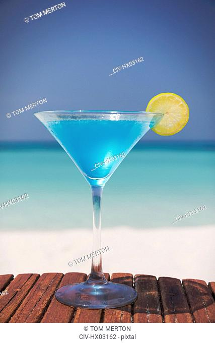 Blue cocktail with lemon slice in martini glass on sunny tropical beach