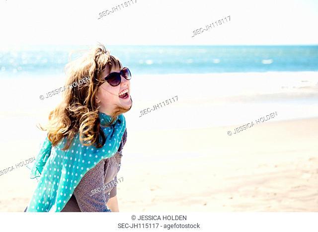 Teenage girl (13-15) laughing on beach