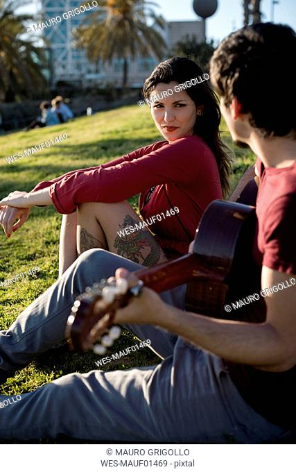 Spain, Barcelona, young woman sitting on a meadow watching boyfriend playing guitar