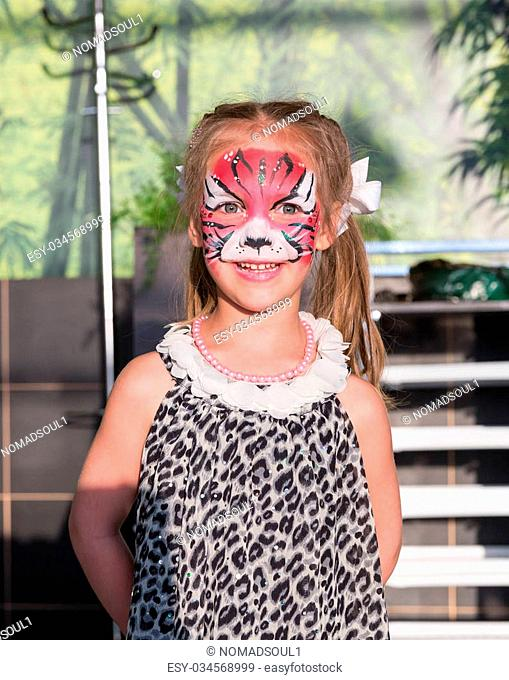 Little girl stands with face painted as a cat