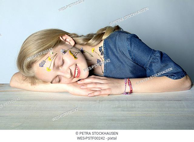 Portrait of smiling blond girl with tattoo of pressed flowers on her face