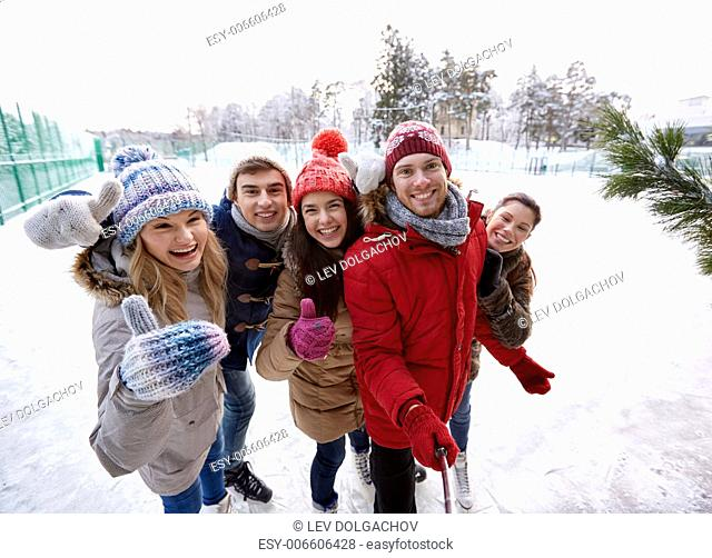 people, friendship, technology and leisure concept - happy friends taking picture with smartphone selfie stick and showing thumbs up on ice skating rink...